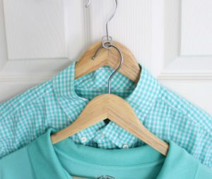 Two shirts hanging on hangers combined with soda can tab.